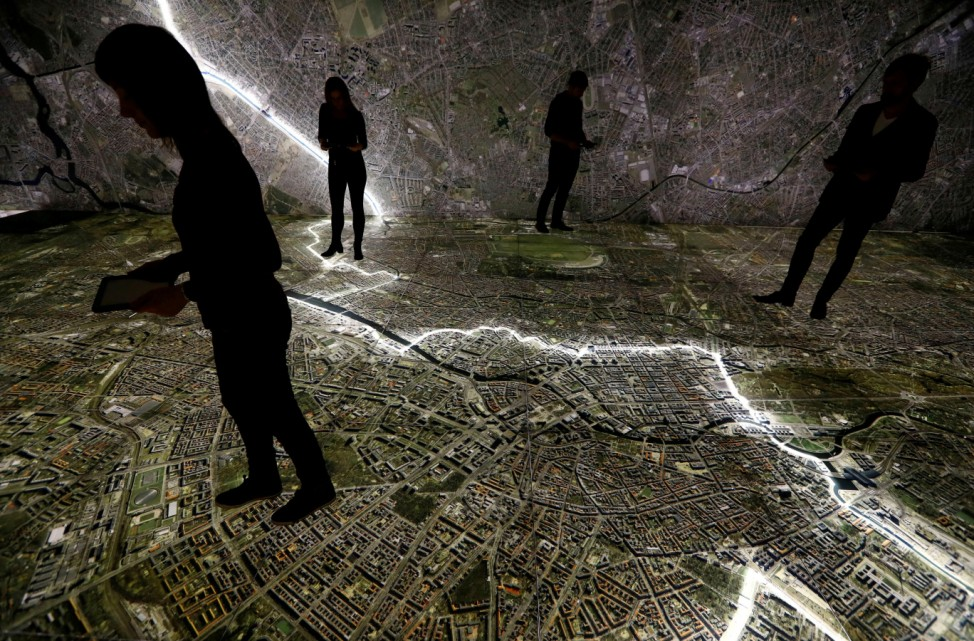 Museum staff members walk with mobile devices over a giant illuminated aerial photograph of Berlin at the exhibition 'The Stasi in Berlin' inside former Stasi prison in Berlin