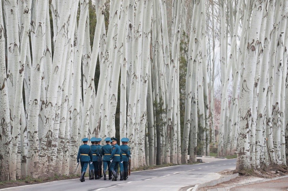 Kyrgyz guards of honour walk away after a welcoming ceremony attended by Presidents Putin of Russia and Jeenbekov of Kyrgyzstan in Bishkek
