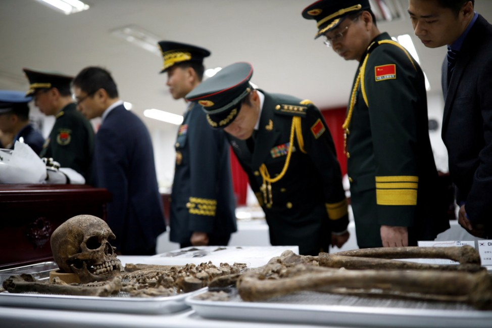 Chinese military officials look at the remains of a Chinese soldier who fought in the Korean War, during the coffin rites in Incheon