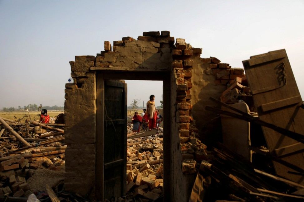 Villagers stand on the debris of the houses after it was hit by a storm in Bara
