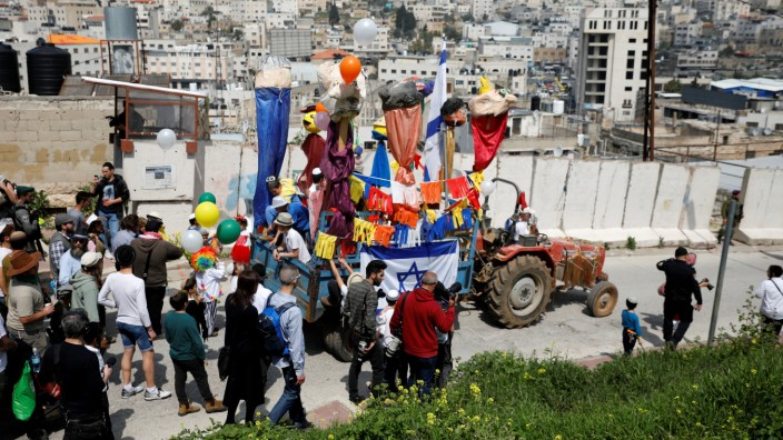 Israeli settlers walk behind a tractor-driven decorated cart as they take part in celebrations marking the Jewish holiday of Purim, in the Israeli-occupied West Bank city of Hebron