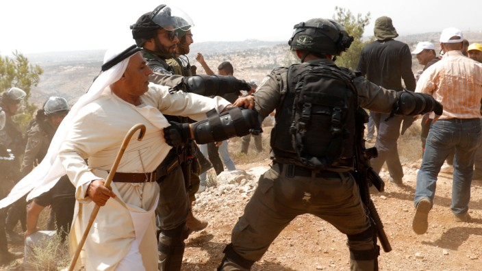 Palestinian demonstrators scuffle with Israeli troops during a protest against Israeli settlement construction, in the village of Ras Karkar, near Ramallah in the occupied West Bank