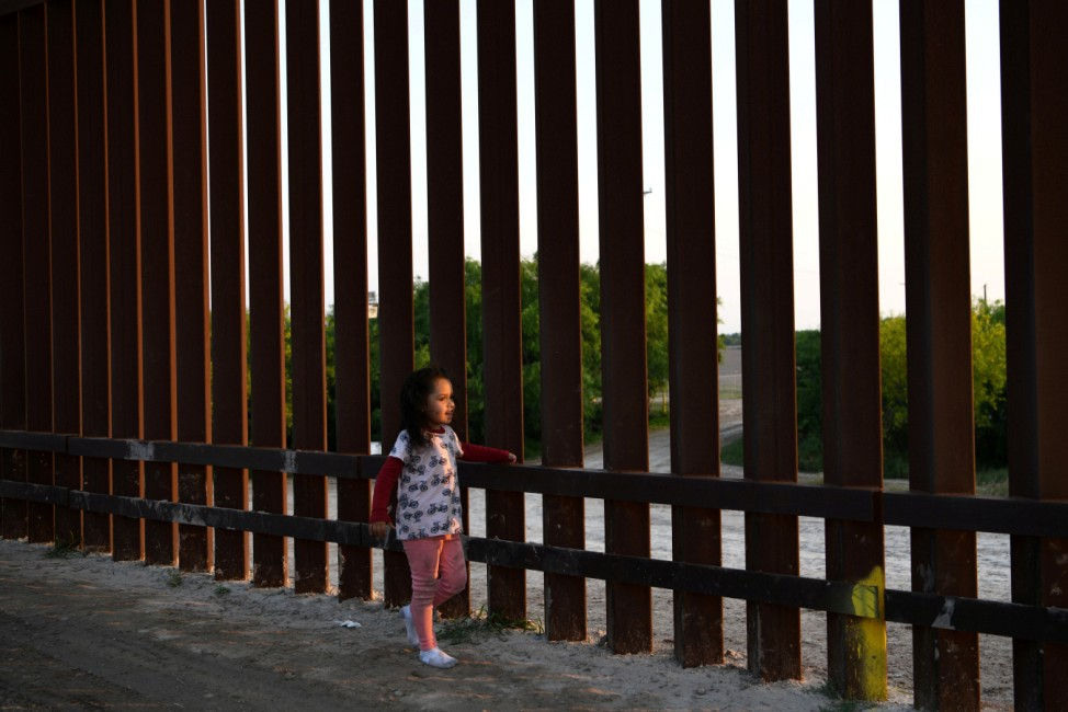 A young girl, part of a group of Central American migrants seeking asylum, walks along a stretch of border fence after illegally crossing the Rio Grande near Penitas