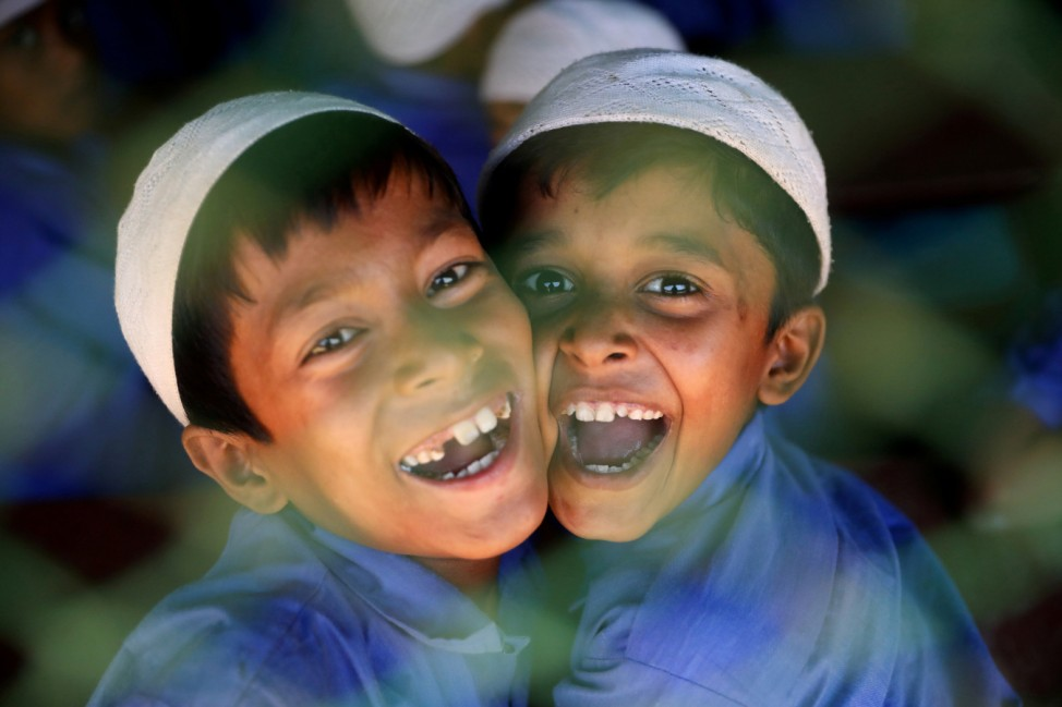 Rohingya refugee boys who study in an Islamic school smile as they react to the camera at a refugee camp in Cox's Bazar