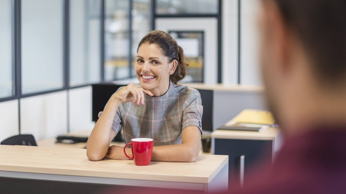 Female employee sitting at desk talking to colleague model released Symbolfoto property released PU