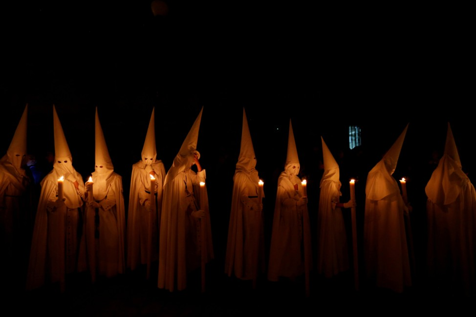 Penitents of La Paz (The Peace) brotherhood take part in a procession during Holy Week in the Andalusian capital of Seville