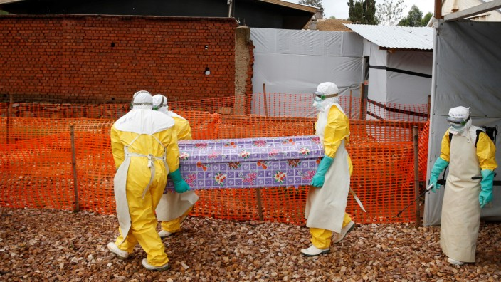 Health workers dressed in Ebola protective suits carry a coffin with the body of Congolese woman Kahambu Tulirwaho, who died of Ebola, as it is transported for a burial from the Ebola treatment centre in Butembo