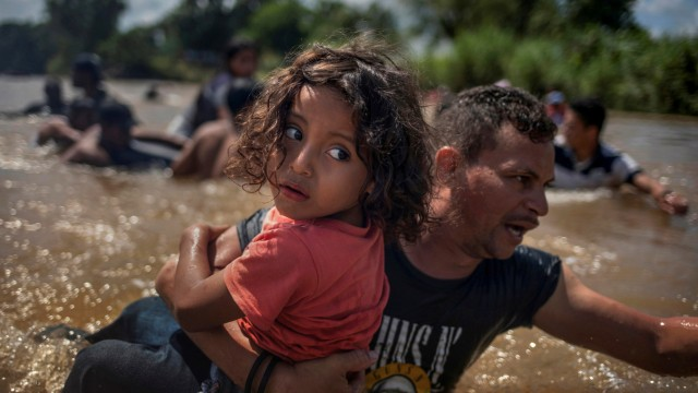 Luis Acosta helps carry 5-year-old Angel Jesus