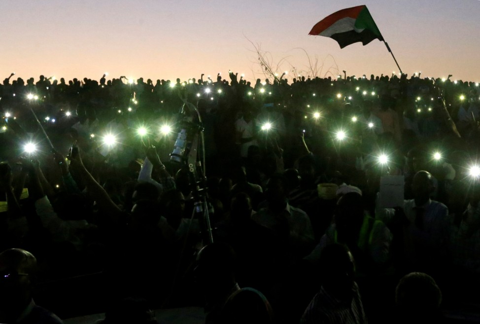 Sudanese demonstrators use their mobile phone torches as lamps as they attend a mass anti-government protest outside the Defence Ministry in Khartoum