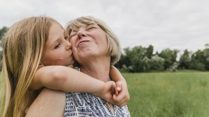 Granddaughter kissing her grandmother model released Symbolfoto PUBLICATIONxINxGERxSUIxAUTxHUNxONLY