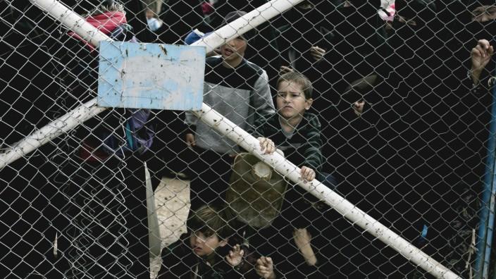 Kinder blicken von dem Tor ins al-Hul-Lager