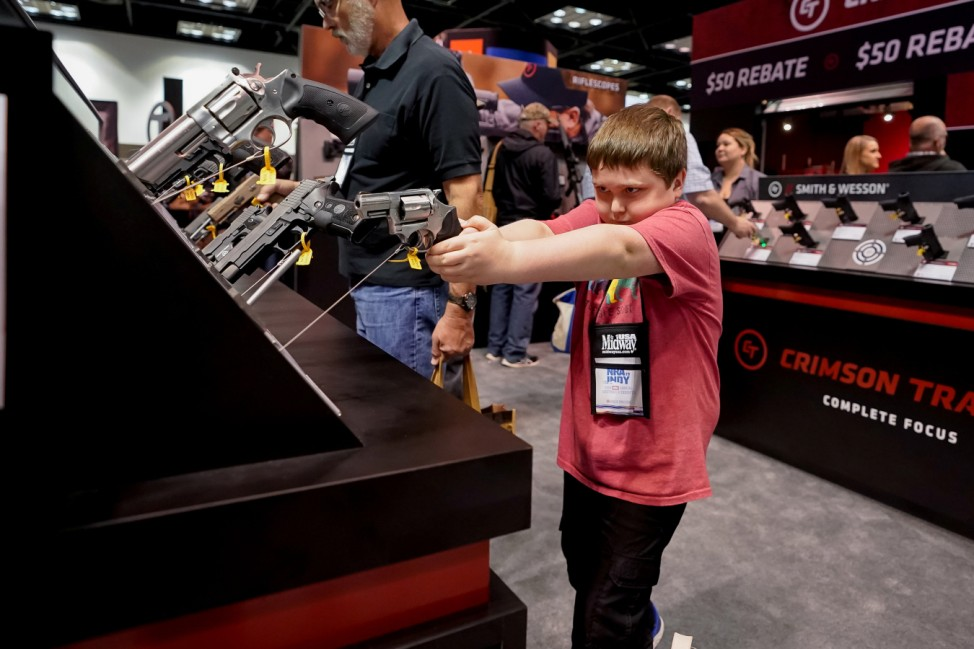 A young attendee handles a handgun during the annual National Rifle Association (NRA) annual meeting at the Indiana Convention center in Indianapolis, Indiana