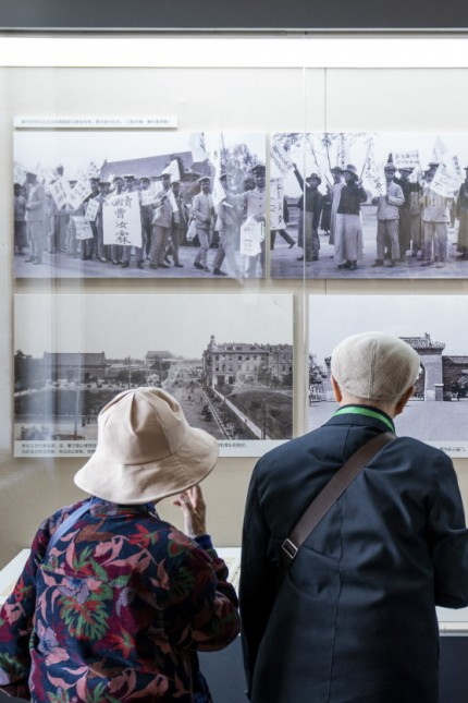 Visitors looking at photos of the May Fourth student protest at the exhibition, 'A Panorama of the May Forth Movement, ' in the New Culture Movement Memorial Museum in Beijing.