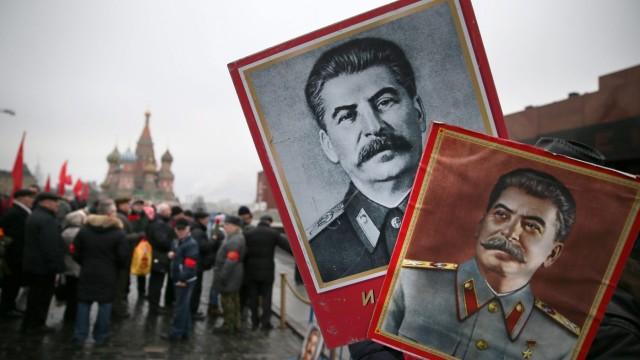 Ein Stalin-Verehrer hält auf dem Roten Platz in Moskau ein Porträt des Ex-Diktators in die Höhe.