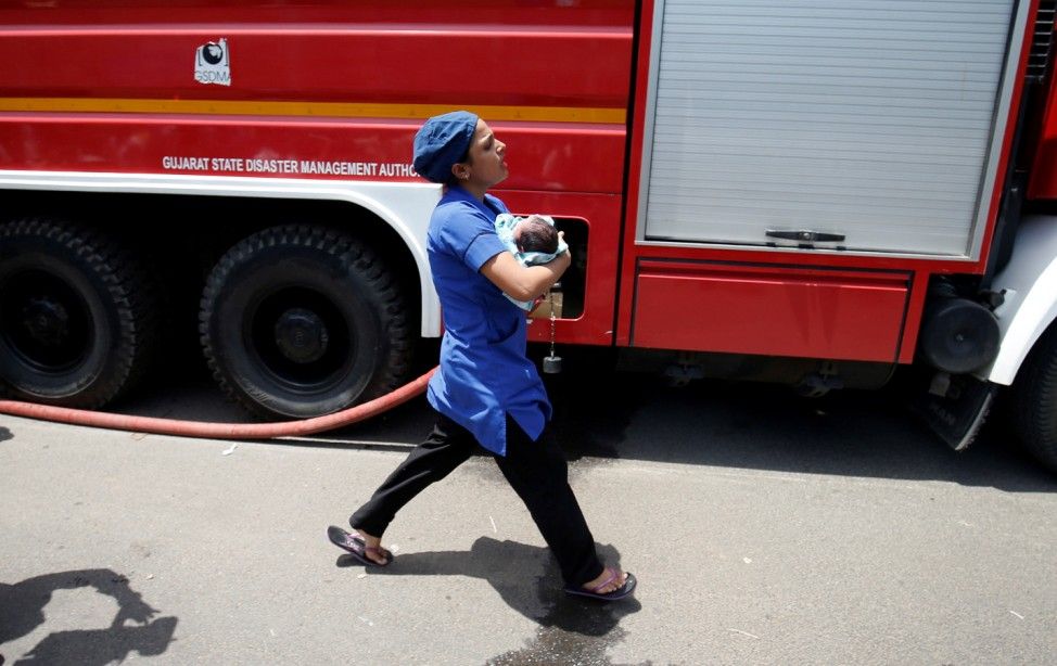 A nurse carries a newborn baby after a fire broke out on the terrace of a children's hospital building in Ahmedabad