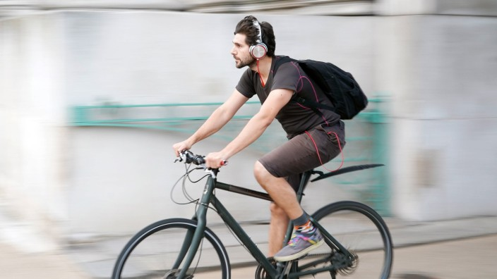 A view of a cyclist riding a bike in Hyde Park Corner while wearing headphones in London UK Photo