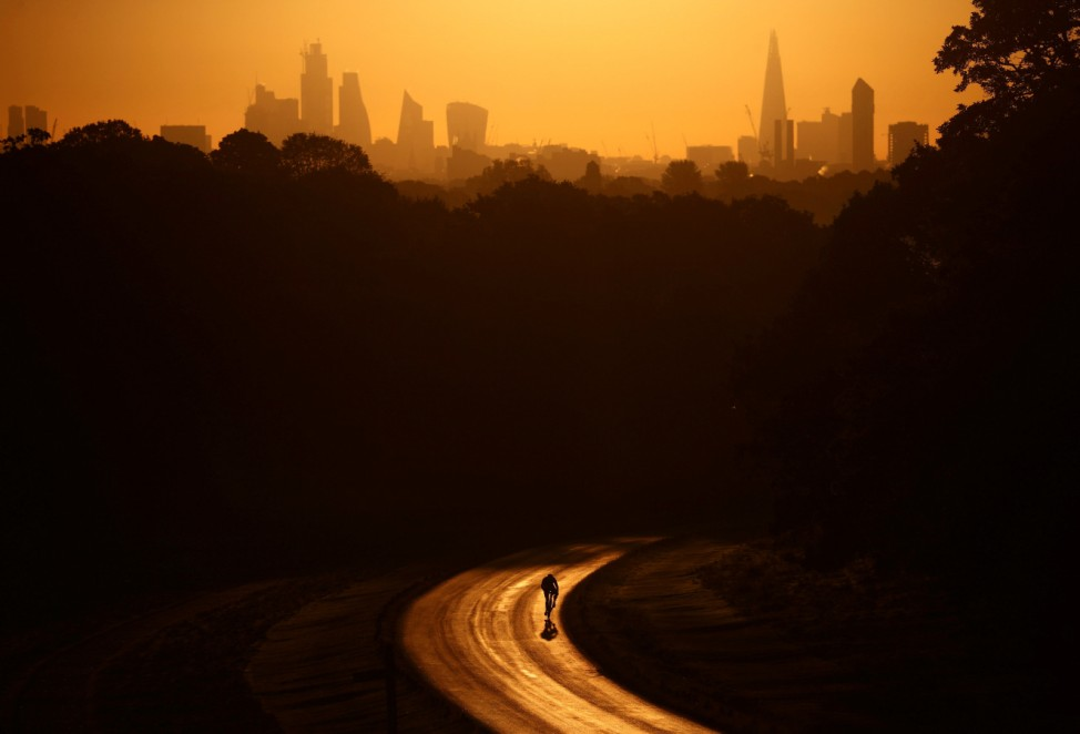The sun rises behind The Shard and the financial district as a cyclist rides through Richmond Park in London