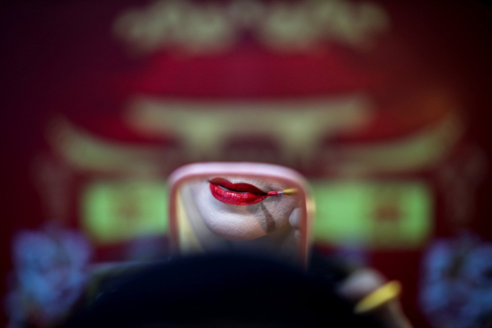 A member of a Chinese opera troupe applies make-up before performing at a shrine in Bangkok