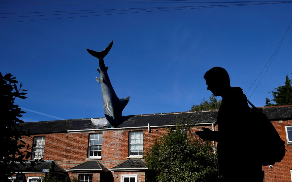 Man walks past a fibreglass sculpture 'Untitled 1986' embedded in the roof of a house in Oxford