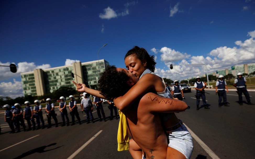 University students kiss as they protest against cuts to federal spending on higher education planned by Brazil's President Jair Bolsonaro's right-wing government in Brasilia