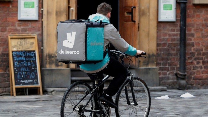 FILE PHOTO: A deliveroo worker cycles along a pedestrianised road in Liverpool
