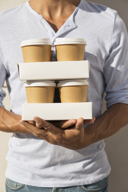 Young man carrying stacks of take away coffee model released Symbolfoto property released PUBLICATIO
