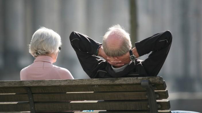 Zwei Senioren sitzen auf einer Parkbank