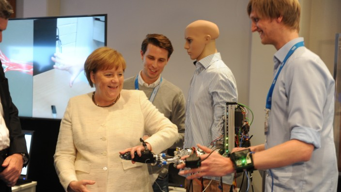 Zauberwort Zukunft: An der Technischen Universität wird Angela Merkel eine Roboterhand gezeigt, die ähnlich feinfühlig reagiert wie eine echte.