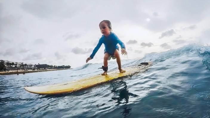 Ein kleiner Junge steht auf einem Surfbrett.