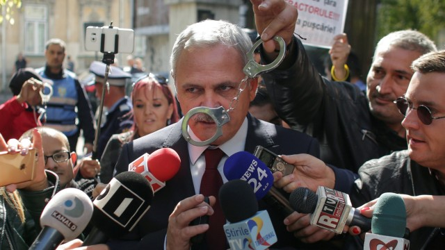 FILE PHOTO: A protester waves a pair of handcuffs in front of Social Democrat Party leader Liviu Dragnea in Bucharest
