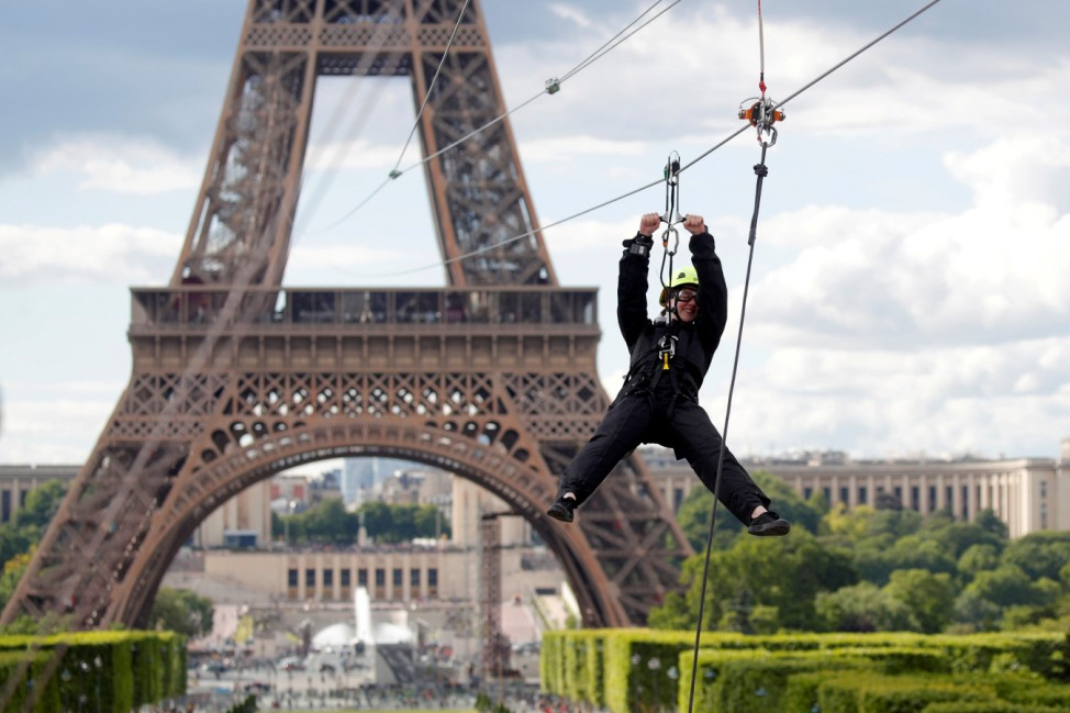 A participant rides a zip line from the second floor of the Eiffel Tower in Paris