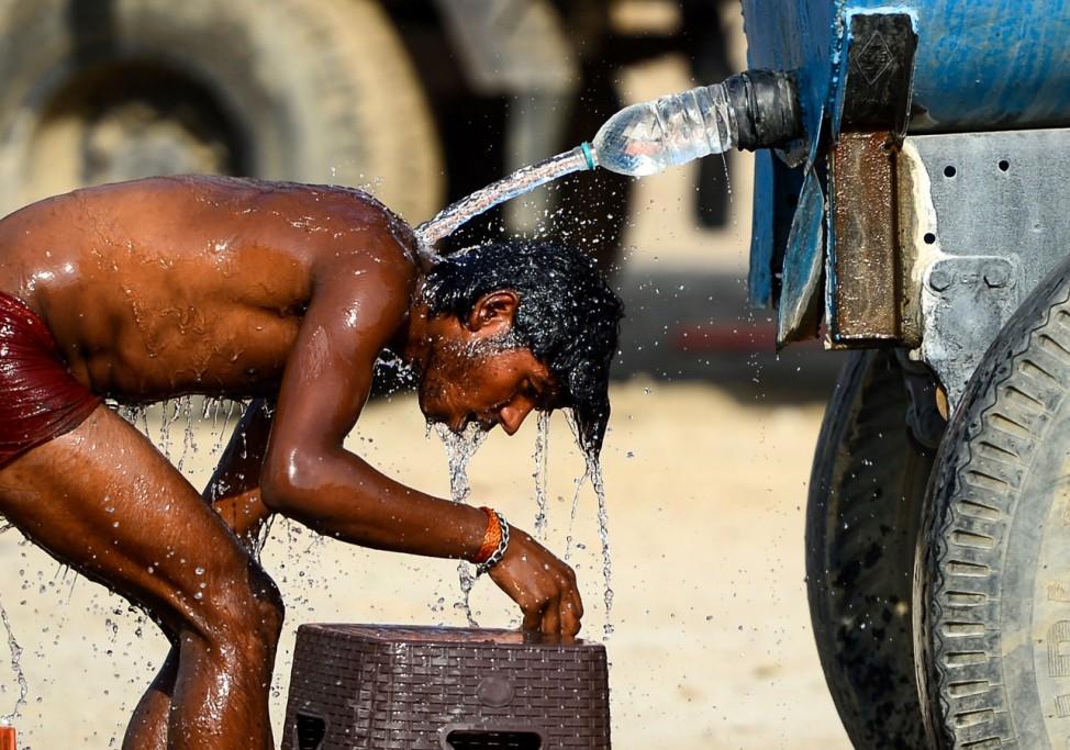 Ein Lastwagenfahrer nimmt im indischen Allahabad eine Dusche aus einer Wasserflasche.