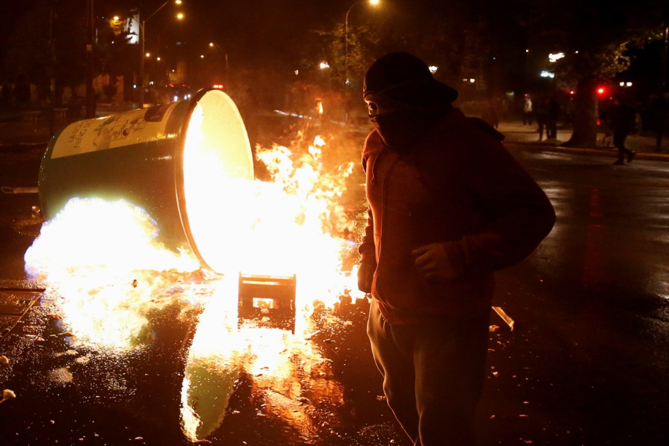A man stands next to a bin set on fire during an anti-government rally as Chile's President Sebastian Pinera delivers a speech inside the national Congress at Valparaiso