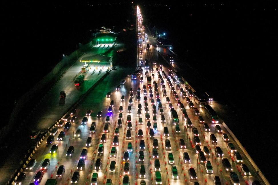 Vehicles queue to enter Cikampek Utama toll gate as people head to their hometowns to celebrate the upcoming Eid al-Fitr in Karawang, West Java province