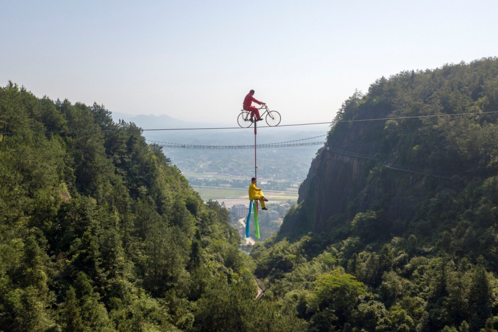 Men perform high-wire stunts on a tightrope in the Shiniuzhai national geological park in Hunan