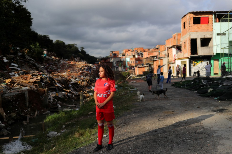 Vitoria Batista Oliveira, 14, stands as she waits for a boy to catch a missing ball during a training session of soccer in Jardim Peri Alto slum, on the outskirts of Sao Paulo