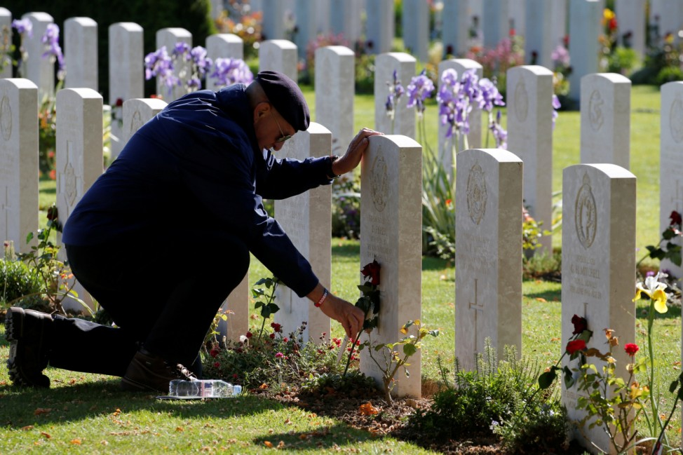 A man places a flower on a tomb before the Royal British LegionâÄÖs commemoration ceremony for the 75th anniversary of D-Day, at the Commonwealth War Cemetery in Bayeux