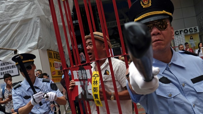 FILE PHOTO: Protesters dressed as Chinese police during a protest to demand authorities scrap a proposed extradition bill with China, in Hong Kong