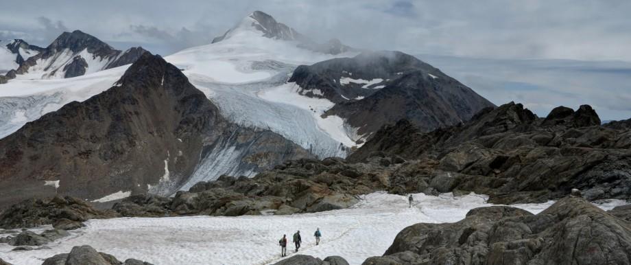 Wanderer queren in den Alpen ein Schneefeld.