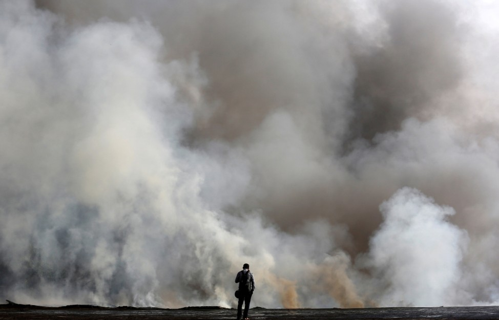 A man stands as he looks at the smoke coming out from a chemical and a cloth warehouse after a fire broke out on the banks of river Ganges in Kolkata