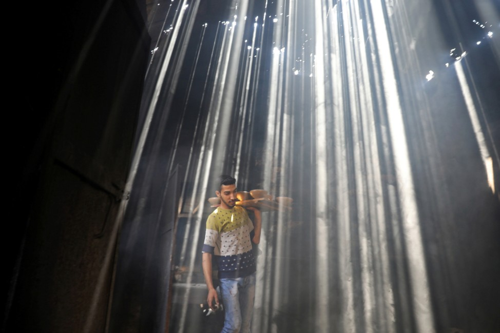 Palestinian worker carries clay pots as the sun rays penetrate through the ceiling of a pottery workshop in Gaza City