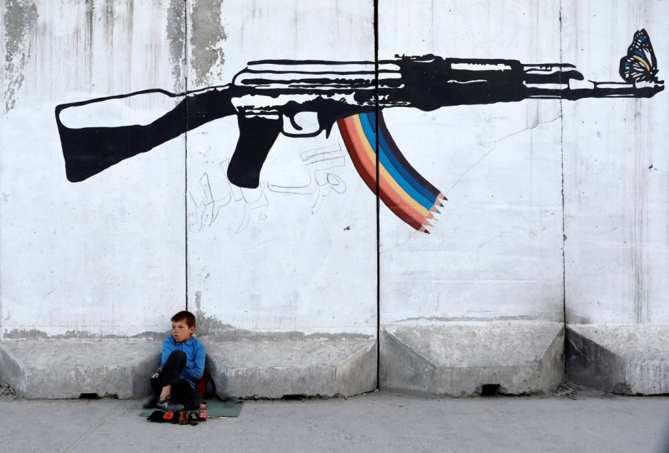 A shoe polisher waits for customers under graffiti on a wall in Kabul