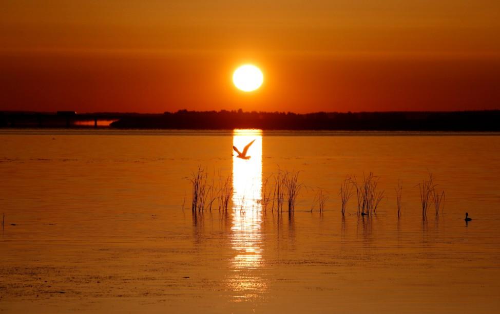 The rising sun illuminates the lake near the town of Vileika