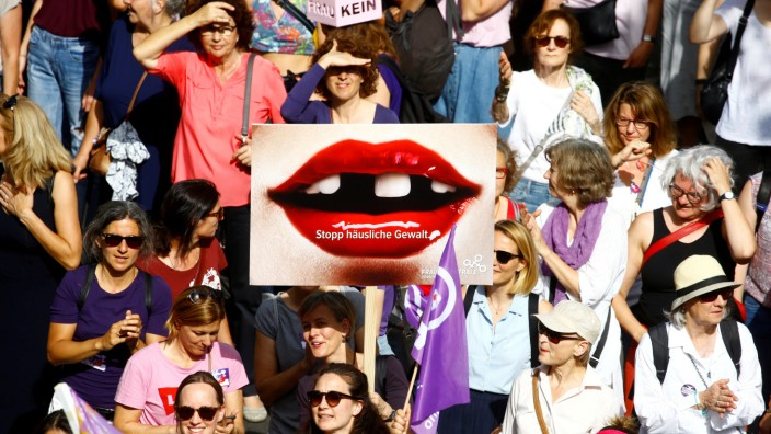 A protester carries a placard reading 'Stop domestic abuse' at a demonstration during a women's strike (Frauenstreik) in Zurich