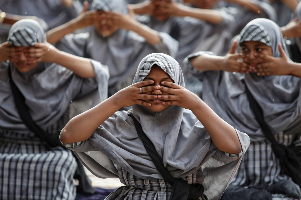 Muslim students attend a yoga lesson at a school ahead of International Yoga Day in Ahmedabad
