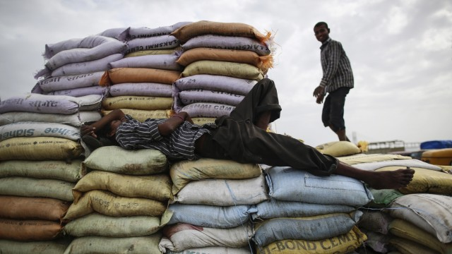 A labourer sleeps on sacks of sand as another works at a market in Mumbai