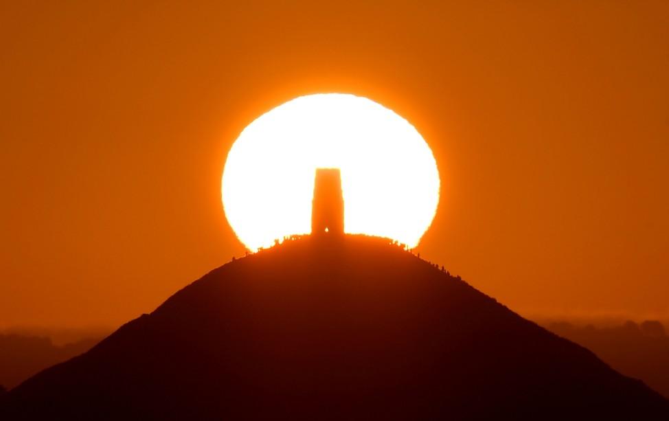 Revellers celebrate the Summer Solstice as the sun rises at Glastonbury Tor in Glastonbury
