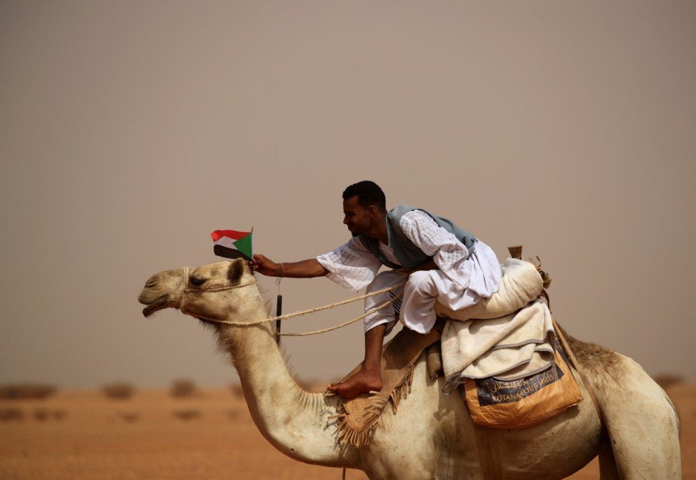 A supporter of Lieutenant General Mohamed Hamdan Dagalo attaches a Sudanese national flag to the head of his camel during a meeting in Aprag village