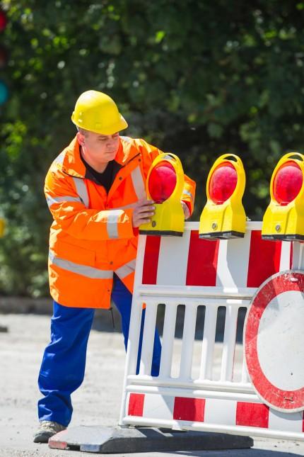 Bauarbeiter in orangener Signalweste eine Strassenabsperrung mit Warnleuchten aufbauend Constructio