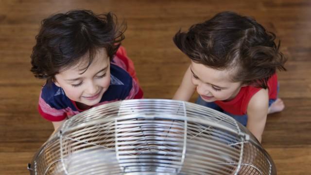 Twin brothers kneeling on the floor in front of fan having fun top view model released Symbolfoto